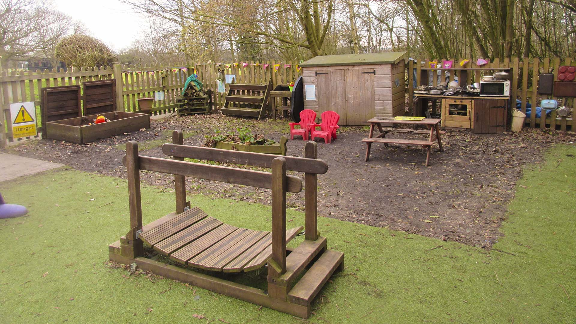 The pre-school 'natural area' featuring digging box, bug hotel, potting shed, and mud kitchen.